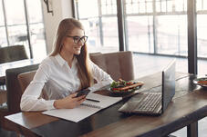 young-cheerful-businesswoman-using-smartphone-and-laptop-in-3874627