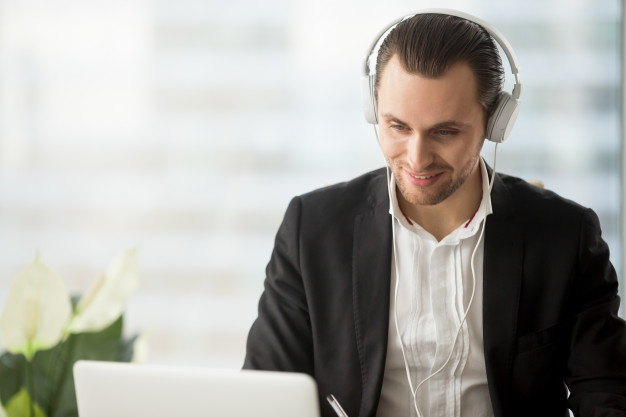 smiling-businessman-headphones-looking-laptop-screen_1163-5436